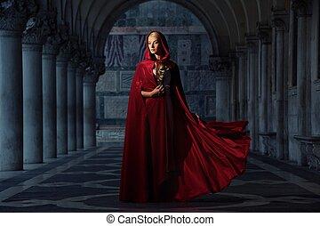 Beautiful woman in red cloak outdoors