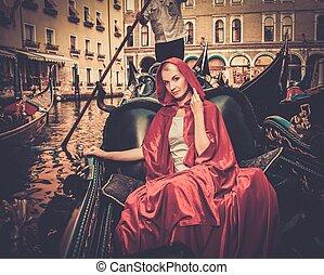 Beautiful woman in red cloak riding on gondola