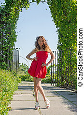 Beautiful woman in red dress in a park