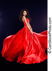 Beautiful woman in red dress isolated on black background. Studio photo. Fashion.