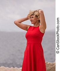 Beautiful woman in red dress near of the sea
