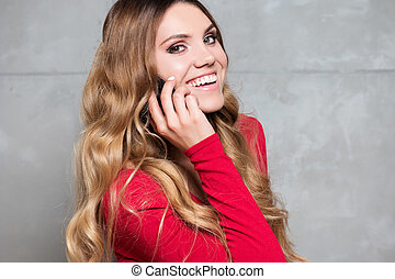 beautiful woman in red dress talks on mobile phone