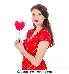 Beautiful woman in red dress with red heart-shaped lollipop