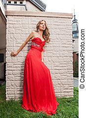 Beautiful woman in red. Full length of attractive young woman posing outdoors