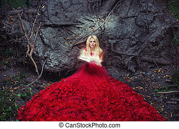 Beautiful woman in red gown reading a book