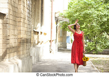 Beautiful woman in red polka dots dress holding basket with sunflowers