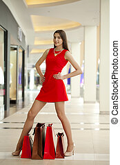Beautiful woman in red sexy dress in the shop