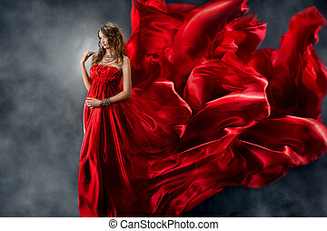 Beautiful woman in red waving silk dress as a flame. Looking down.