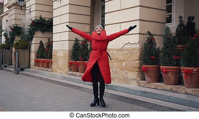 Beautiful woman in red winter jacket walks along the street covered with snow in a beautiful old European city