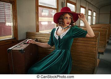 Beautiful woman in retro train, old wagon interior