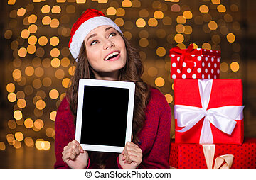 Beautiful woman in santa claus hat with tablet blank screen