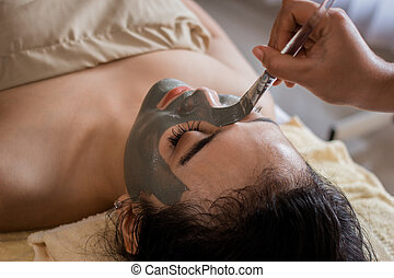 woman in spa salon getting face mask by beautician