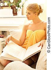 beautiful woman in spa salon with book