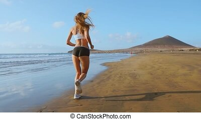 Beautiful woman in sports shorts and t-shirt running on the...