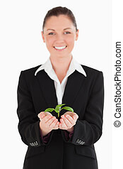 Beautiful woman in suit holding a small plant