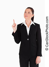 Beautiful woman in suit pointing at a copy space