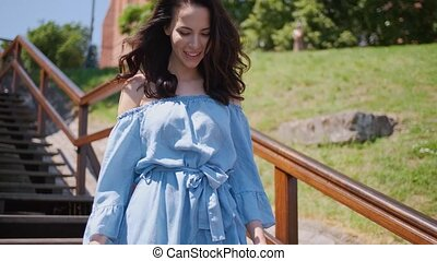 Beautiful woman in summer fashion dress walking on stairs in...