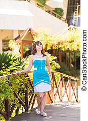 Beautiful woman in summer outfit posing in luxury resort . Holiday vacation mood. Bright blue dress.