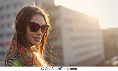 Beautiful woman in sunglasses standing on balcony and smiling on a camera.
