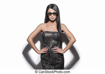 Beautiful woman in sunglasses. Waist up of attractive young woman in sunglasses holding her hands on hip while isolated on whiteBeautiful woman in sunglasses. Waist up of attractive young woman in sun