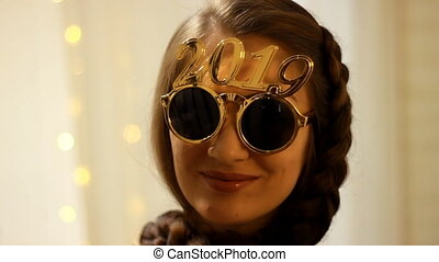 Beautiful woman in sunglasses with the number 2019 smiles in...