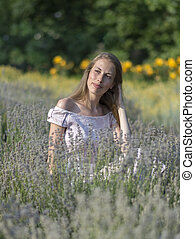 Beautiful woman in sunny day wearing pink dress and sitting in fresh lavander field, enjoying beauty of nature