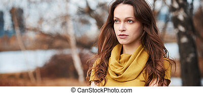 Beautiful woman in the autumn city park