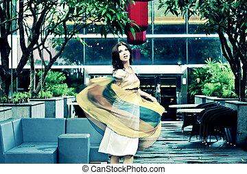 Beautiful woman in the garden dancing