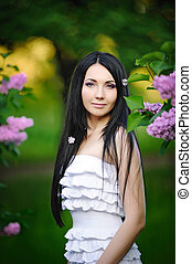 Beautiful woman in the garden of blooming lilacs