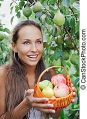 Beautiful woman in the garden with apples and pears in the crib