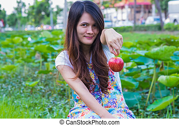 Beautiful woman in the garden with apples