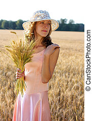 Beautiful woman in the hat holding wheat ears in her hand
