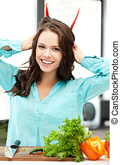 beautiful woman in the kitchen cutting vegetables
