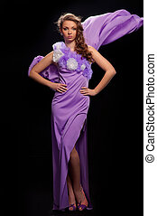 beautiful woman in the purple dress on a gray background