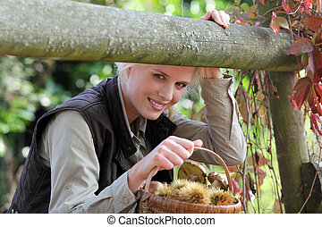Beautiful woman in the woods with basket of chestnuts