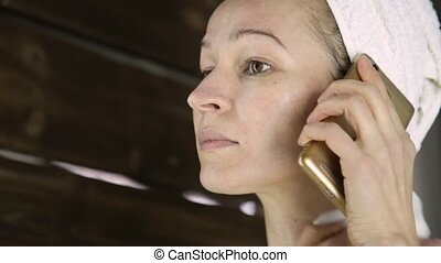 beautiful woman in towel cleaning her face with a cotton pad and talking on a phone