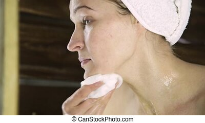beautiful woman in towel cleaning her face with a cotton pad. girl wash off mask from face.