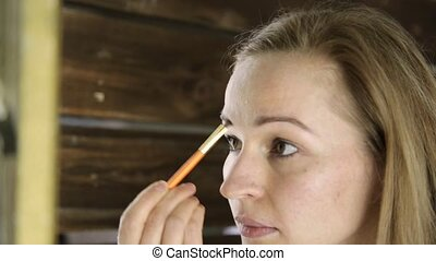 Beautiful woman in towel, paints her eyebrows in front of mirror