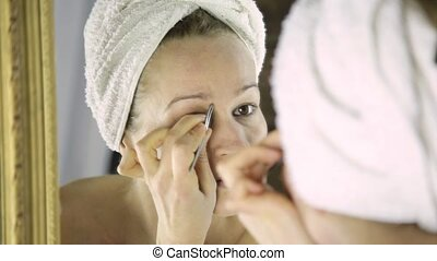beautiful woman in towel plucking her eyebrows. Skin care and home Spa