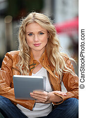 Beautiful woman in town using electronic tablet