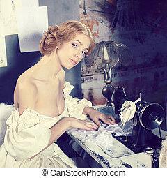 Beautiful woman in vintage dress is in clothing design studio