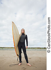 Beautiful woman in wet suit holding