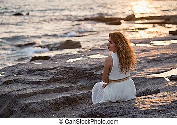 Beautiful woman in white dress enjoying sunset