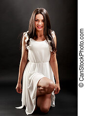 Beautiful woman in white dress on black background