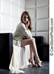 Beautiful woman in white dress sitting on sofa