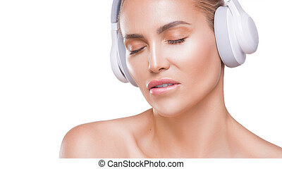 beautiful woman in white headphones enjoing music, bit her lip, with closed eyes on white background