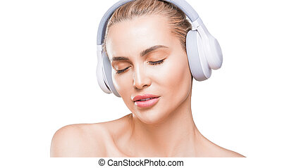 beautiful woman in white headphones listens to music with closed eyes on white background