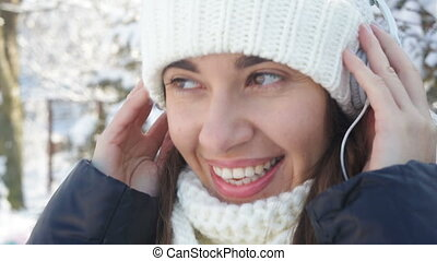 beautiful woman in white knitted hat listening to music on headphones