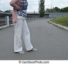 Beautiful woman in white pants posing in the summer