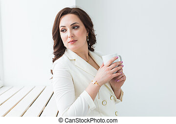 Beautiful woman in white suit holding big white cup of cappuccino coffee.